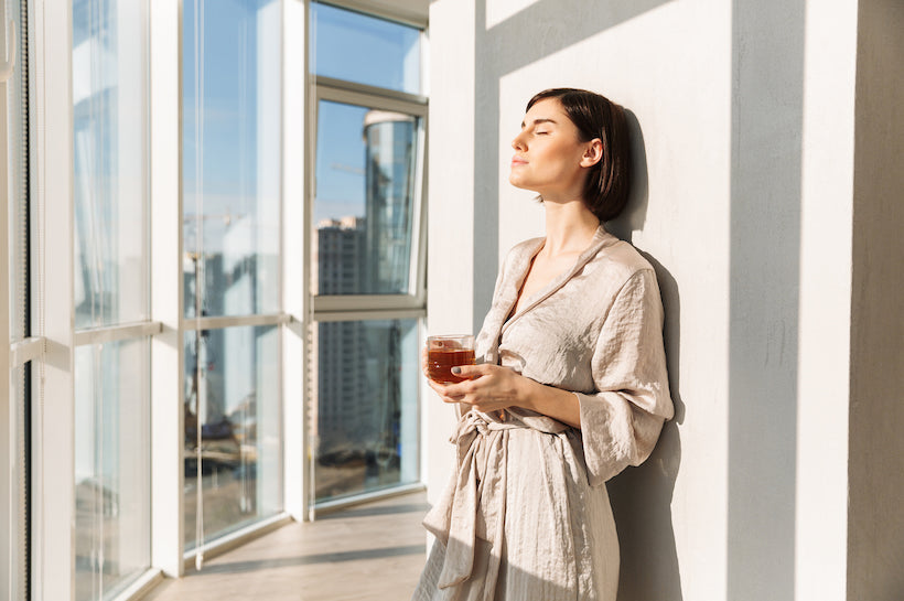 Elegant woman with short dark hair in housecoat holding glass of tea and enjoying sunny weather, while standing near window in posh apartment