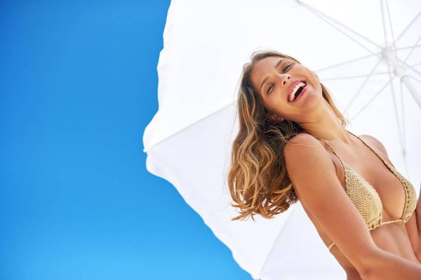 Blonde woman smiling and holding a white umbrella