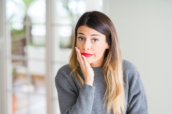 Woman with red lipstick and gray sweater holding her face in doubt