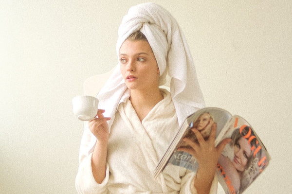 Woman in bath robes and with towel on her head holding a magazine with one hand and a coffee cup with the other one.