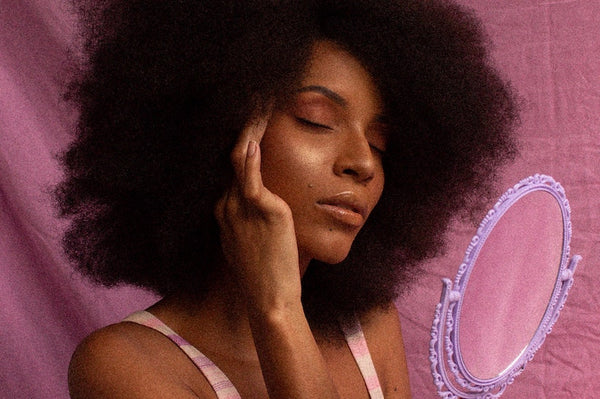 African American woman holding a mirror with eyes closed on a purple background