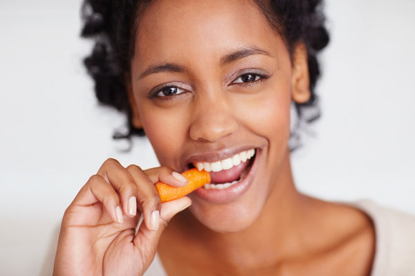 Happy young African American female eating a carrot