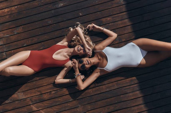 Two women in bathing suits, laying on the ground, laughing and having fun.
