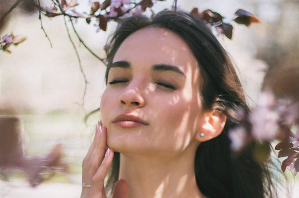 Woman touching her face, eyes closed, flowers on a tree.