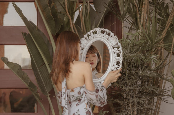 Asian young woman looking at a mirror. Pink room with plants on the background.