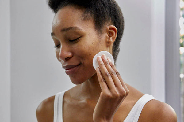 woman using a cotton pad to clean her skin