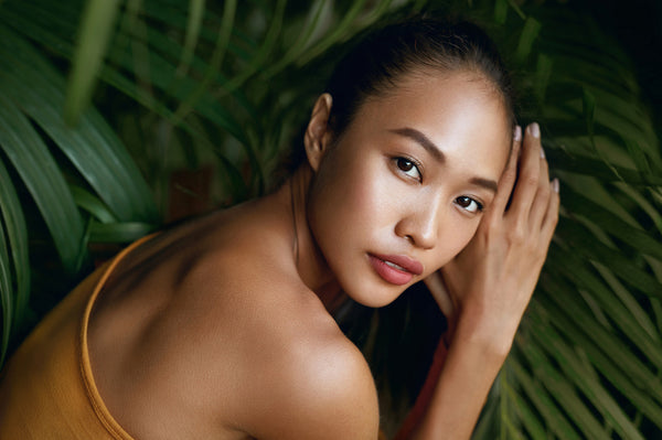 Beautiful asian girl portrait with jungle leaves on background. Natural makeup and healthy skin in tropical nature.