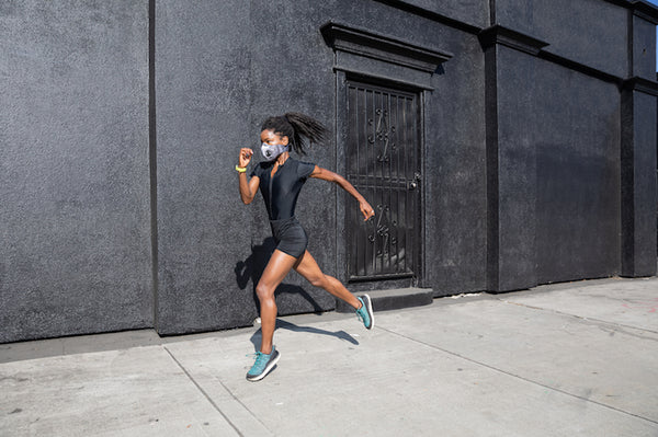 Fit African American woman running with a face mask.