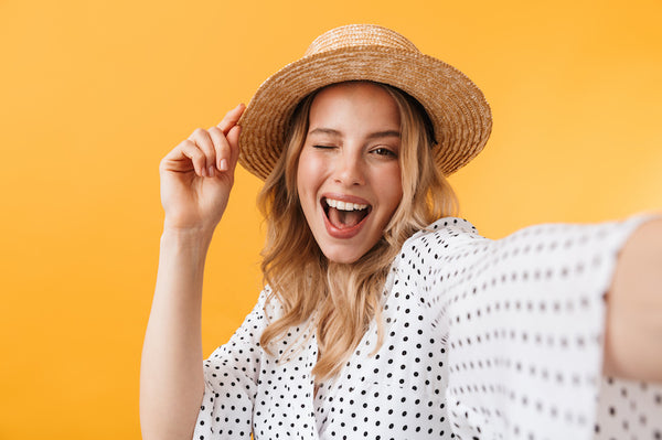 Blonde woman selfie smiling and winking while holding her brimmed hat with one hand