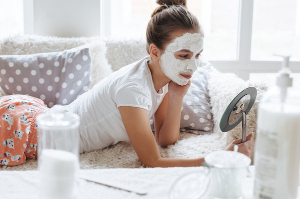 Woman in pajamas with face mask on looking at mirror