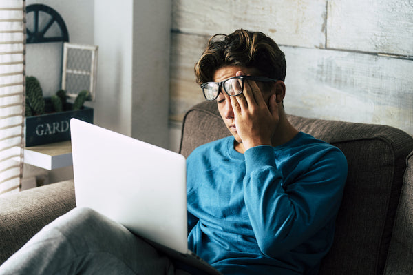 Man using his laptop and looking stressed