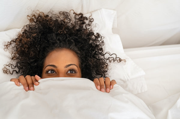 Woman with curly hair laying in bed, pulling a blanket up to her eyes
