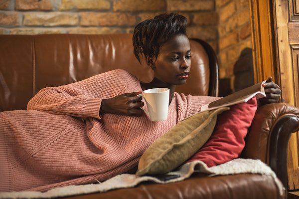 Young African American woman relaxing on sofa at home and reading a magazine during her coffee time.