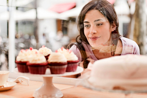 Woman looking at cup cakes display in window