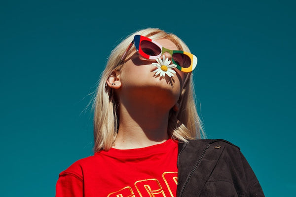 Blonde teenage girl wearing a red t-shirt, colorful sunglasses and flower on mouth looking up