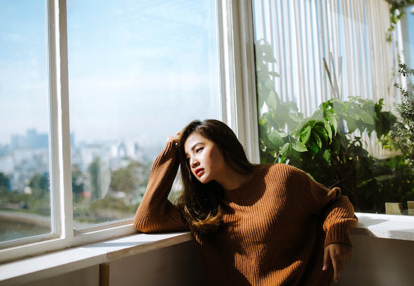 Stressed young Asian woman looking out of a window.