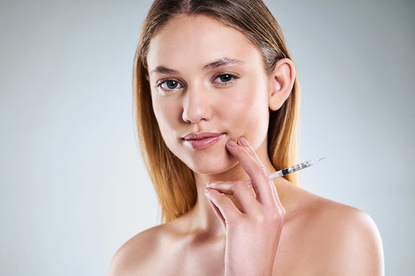 Woman holding botox needle