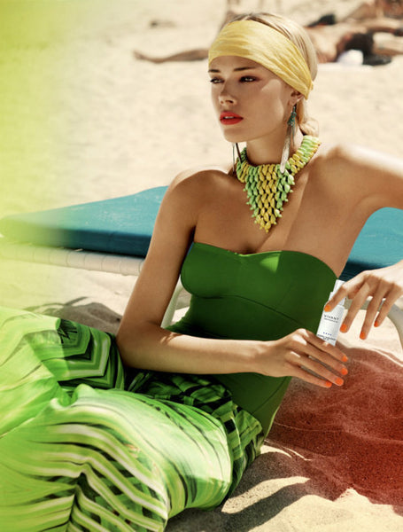 Woman in a green gown and holding Vivant's New Mineral Sunscreen SPF 30.