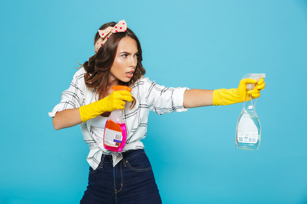 Woman holding two cleaning bottles and pretending to spray