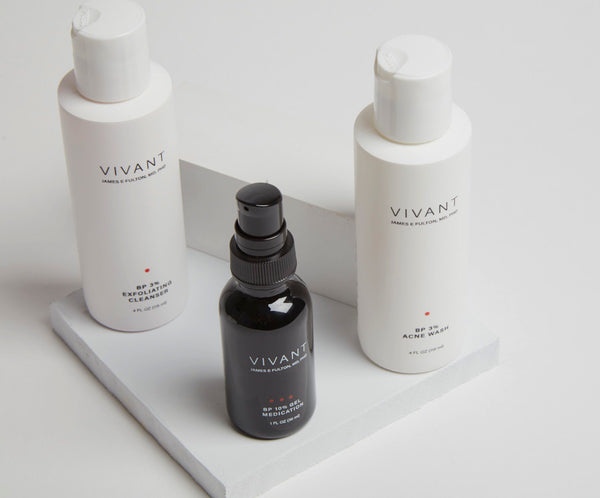Vivant's benzoyl peroxide treatments. Two white bottles of cleanser and a serum in a black bottle. Studio shot.