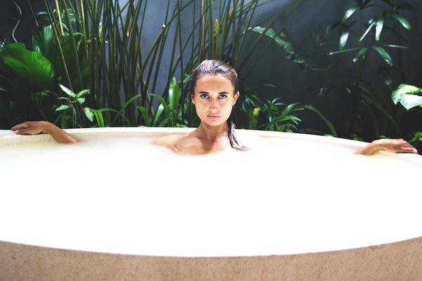 Woman inside a tub taking a milk bath with plants on the background