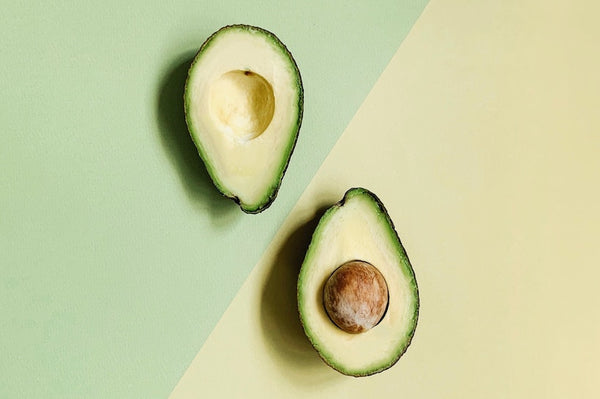 Avocado cut in half over light green and yellow