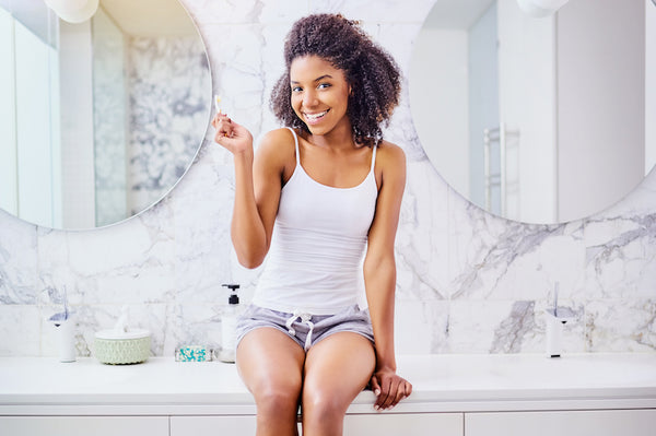 Woman sitting on bathroom counter smiling at camera