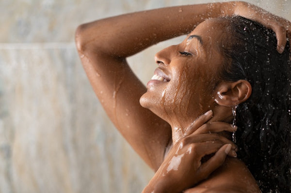 Woman showering, smiling and washing her hair.