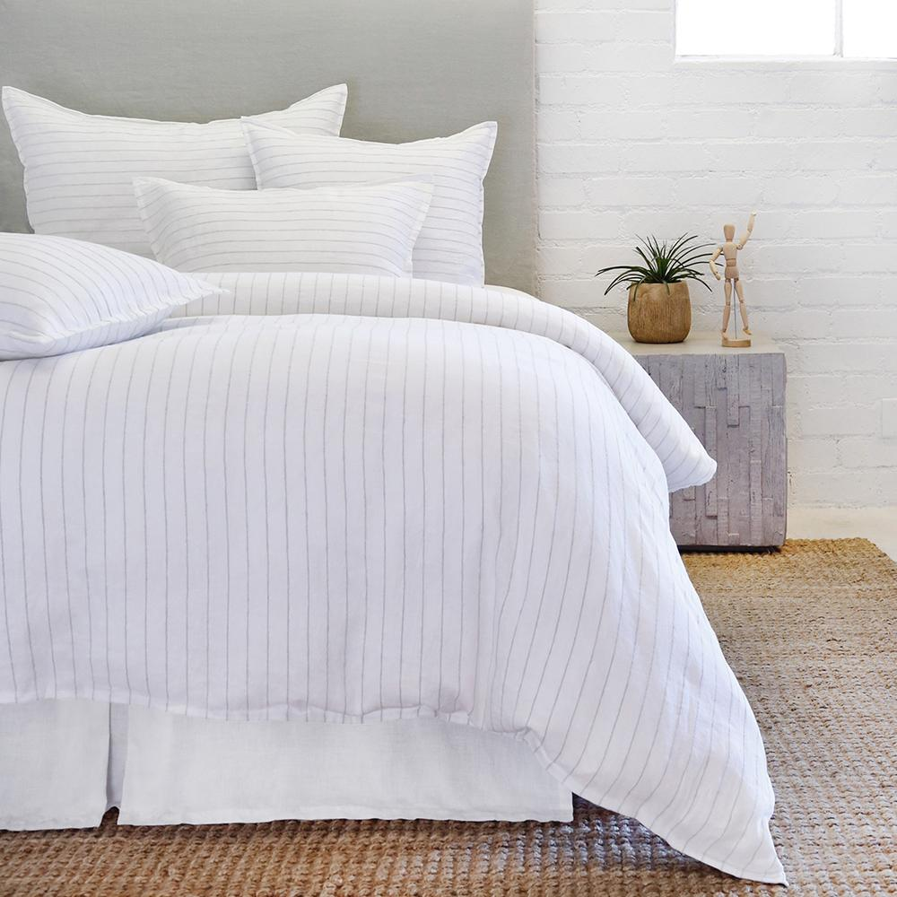 striped white and ocean bedding on a bed, duvet and 4 pillows