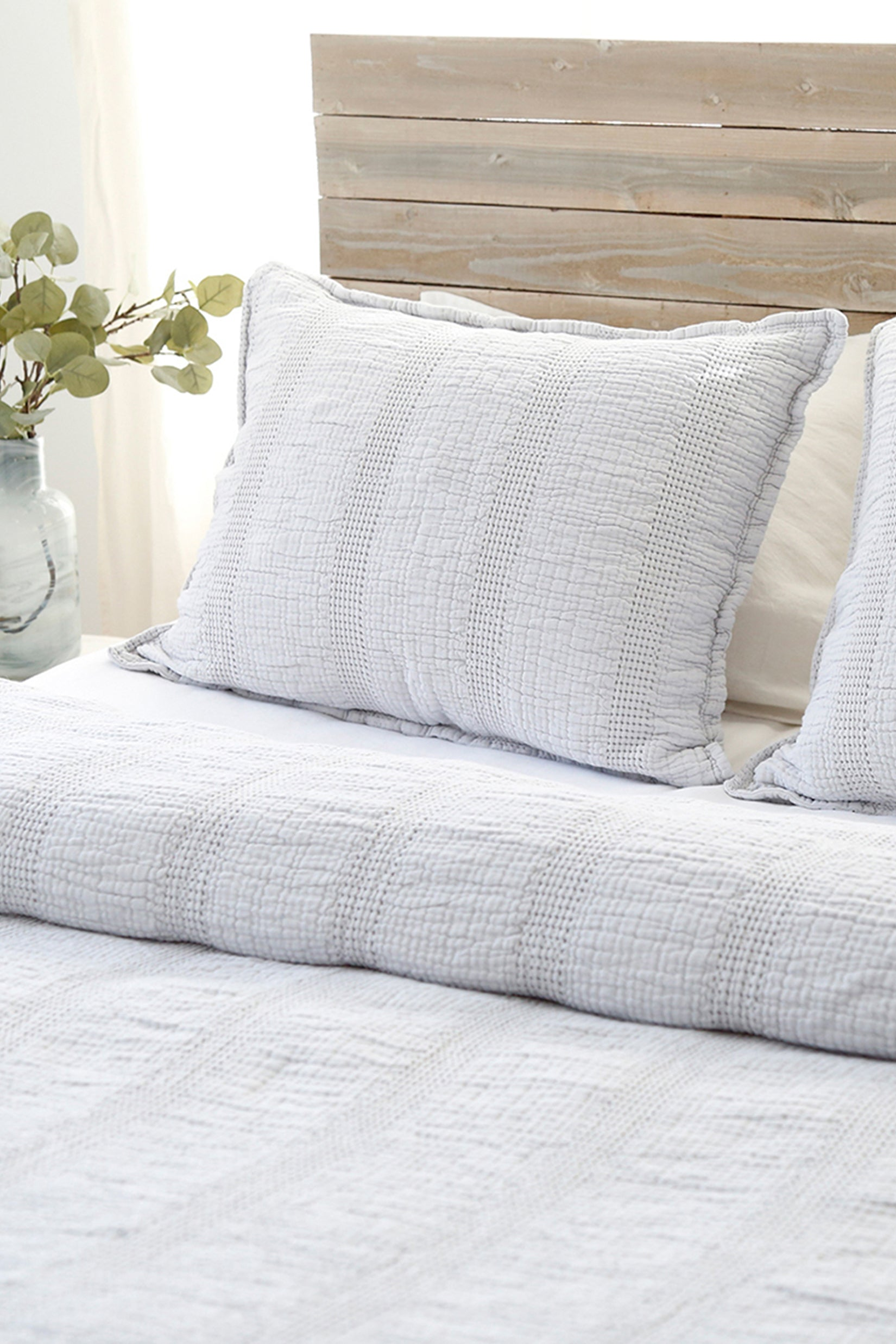 Light grey bedding on a bed