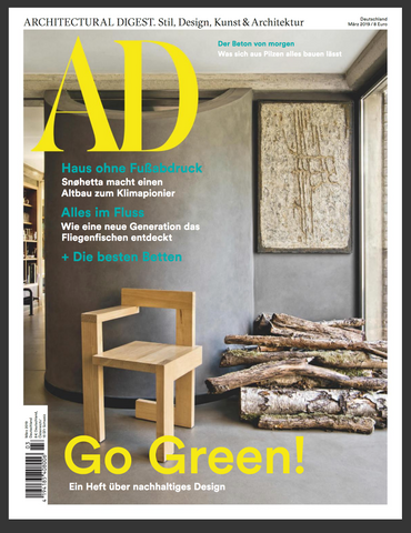 Cover of AD magazine, inside a modern home a grey wall with a modern wooden chair next to a pile of logs for a fire