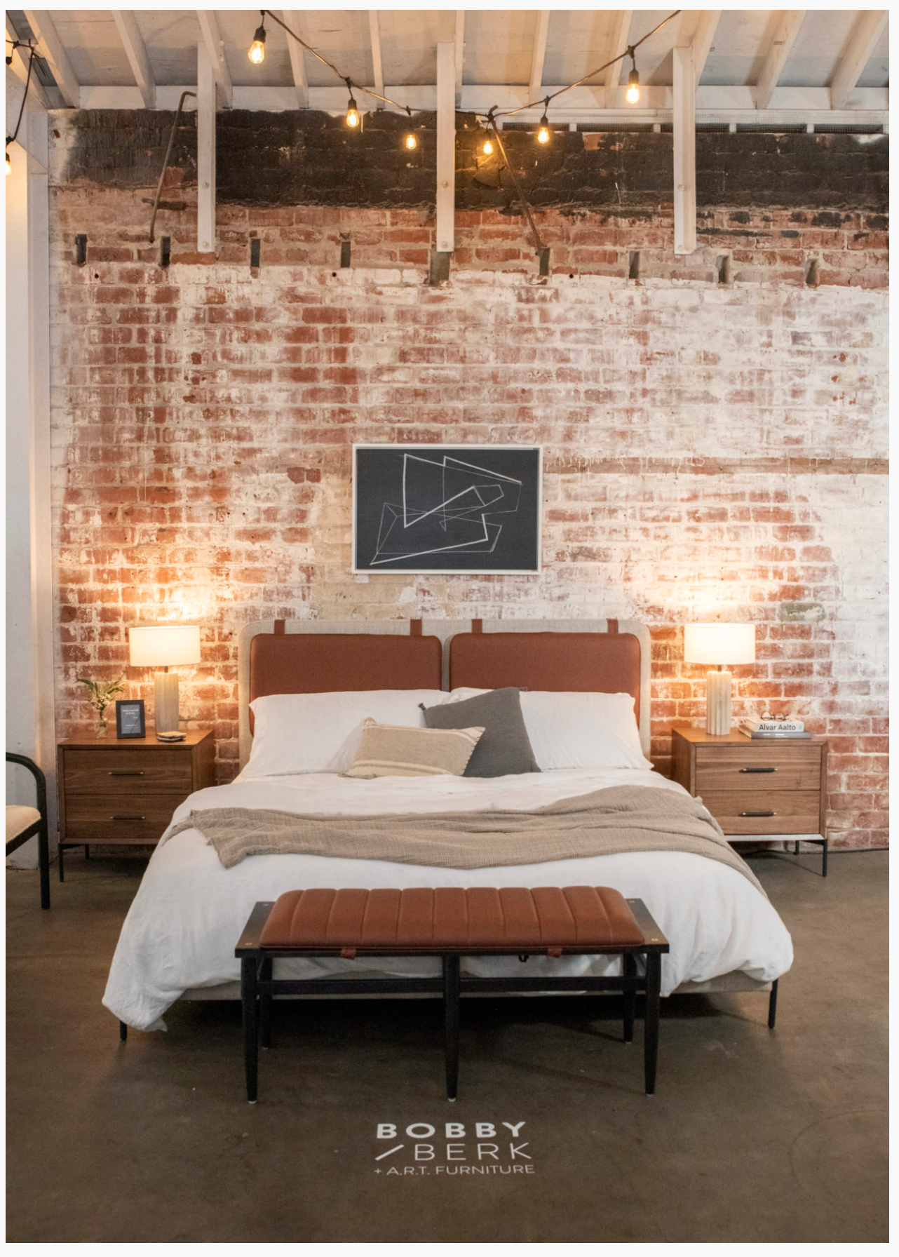 A modern bed in front of a red brick wall