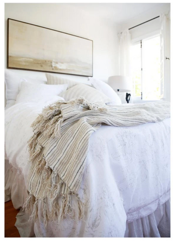A corner of a light colored bed with a striped throw draping