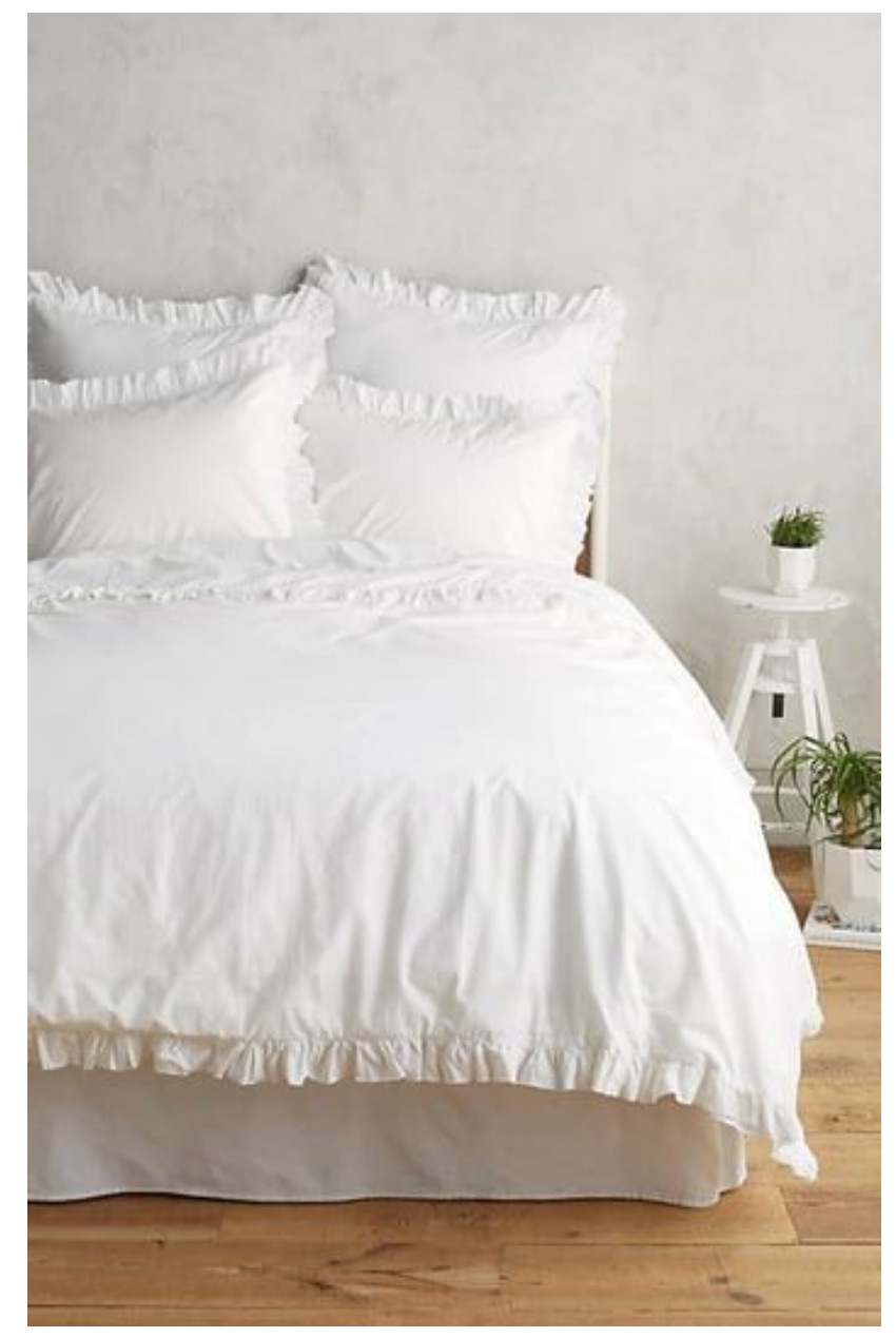 White ruffle bedding on a bed