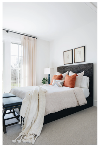 A light and airy bedroom with white bedding and orange pillows