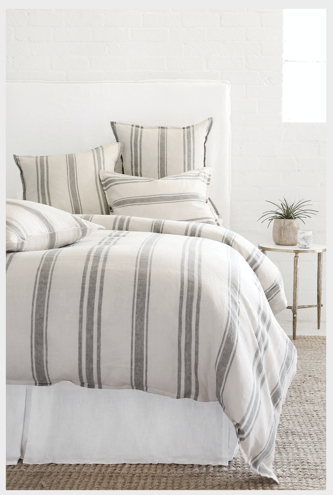 A bed with a big fabric head board, with flax and midnight striped duvet and pillows