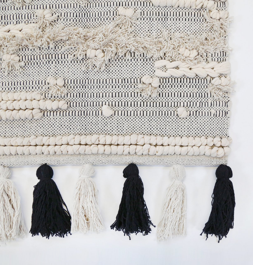 the corner of a handwoven rug with tassels