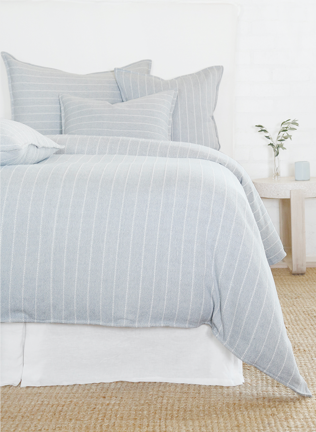 Light blue striped bedding on a bed
