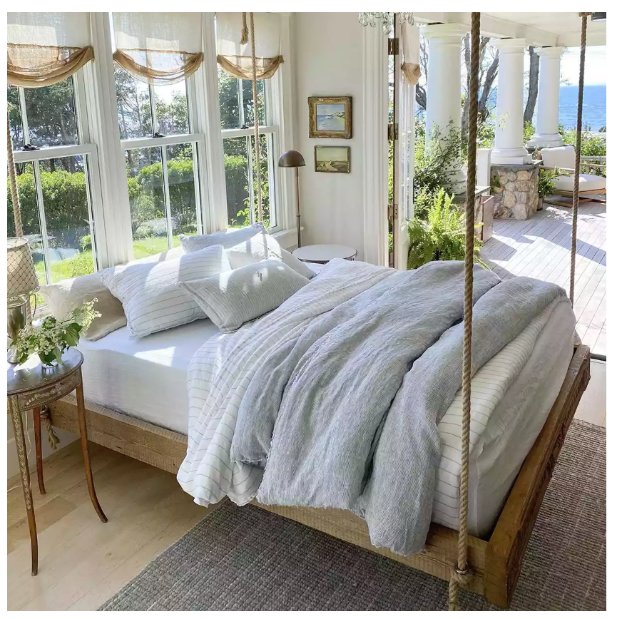 A bed swinging from ropes in a cape code home