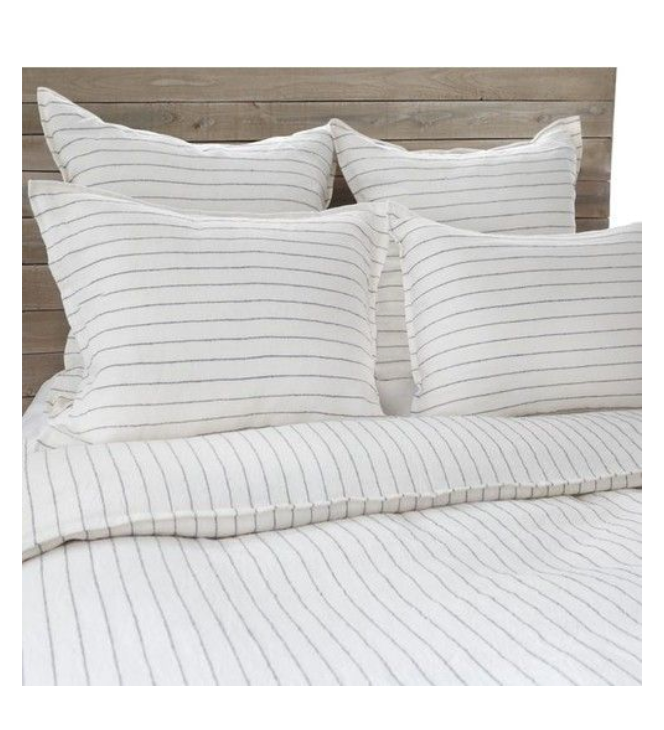 A bed with a striped duvet and four pillows.