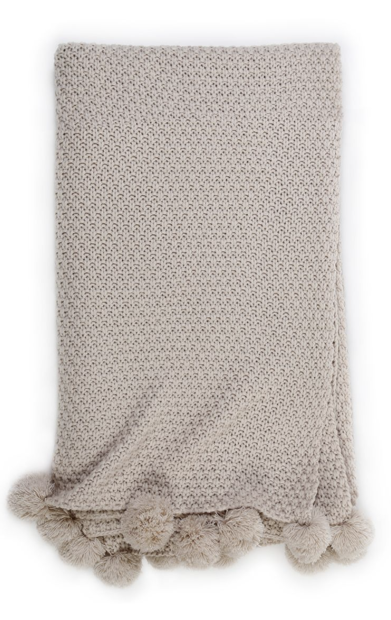 A knit taupe throw with pom poms on the edge.