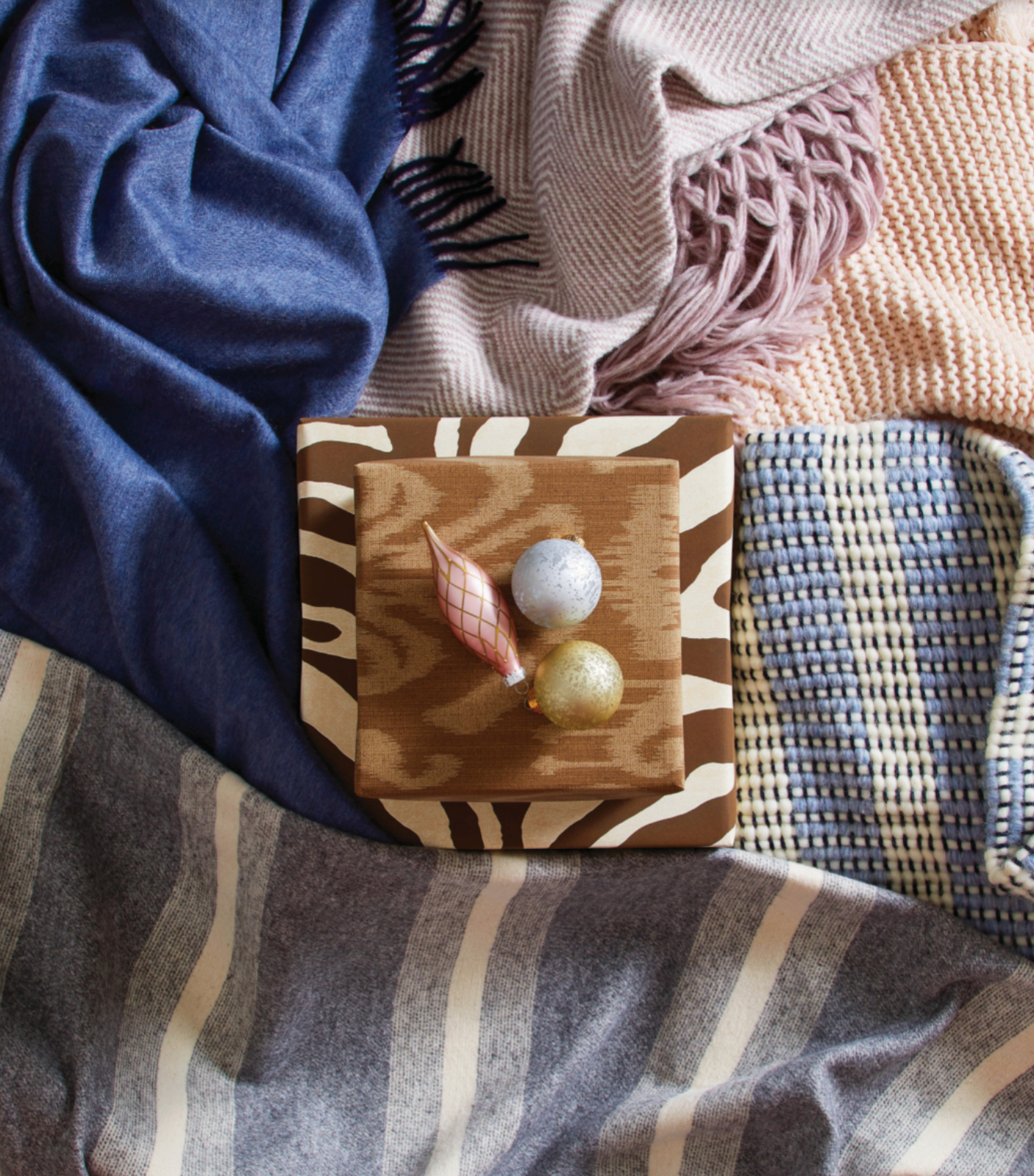colored fabric draped around a box with three ornaments laying on it