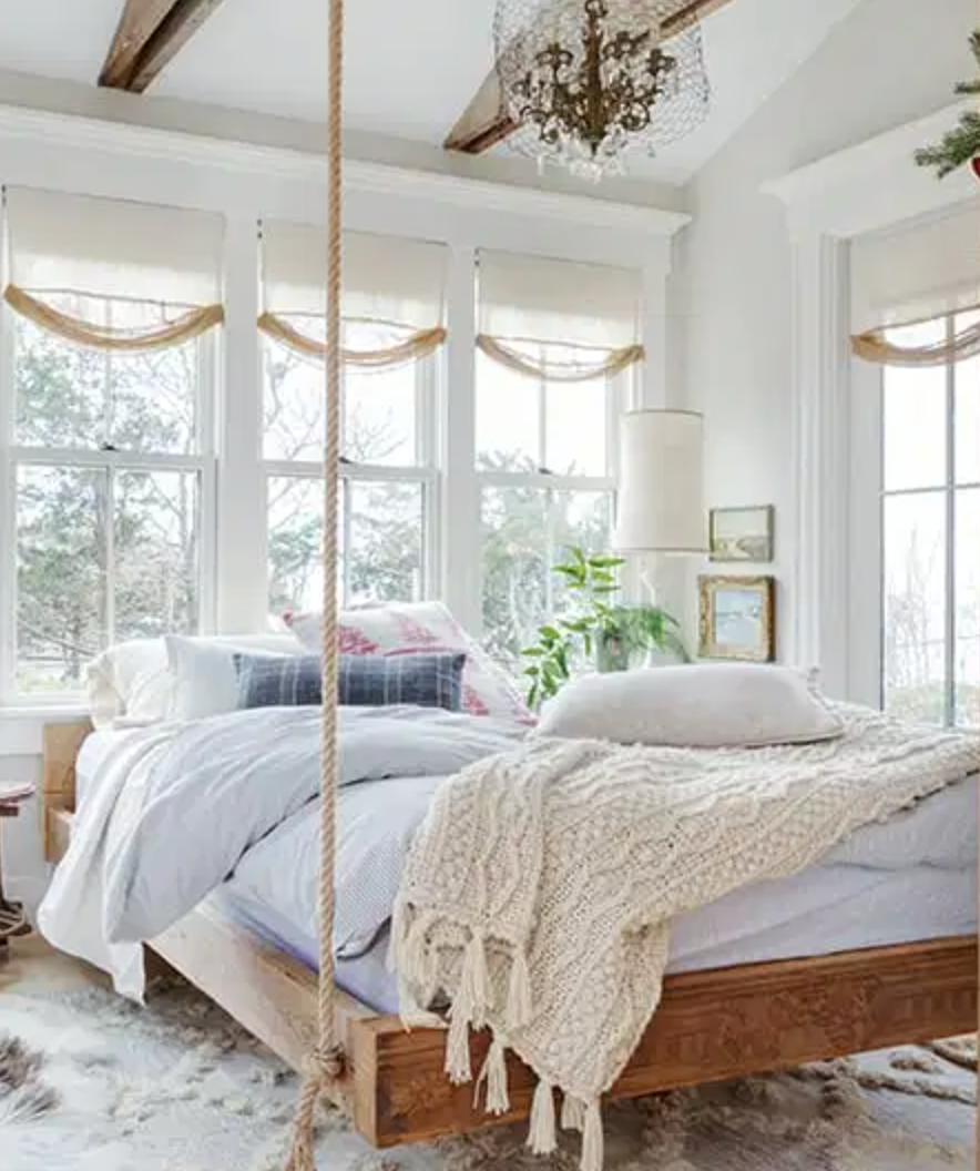 a wooden platform bed hanging by ropes in a cape cod bedroom