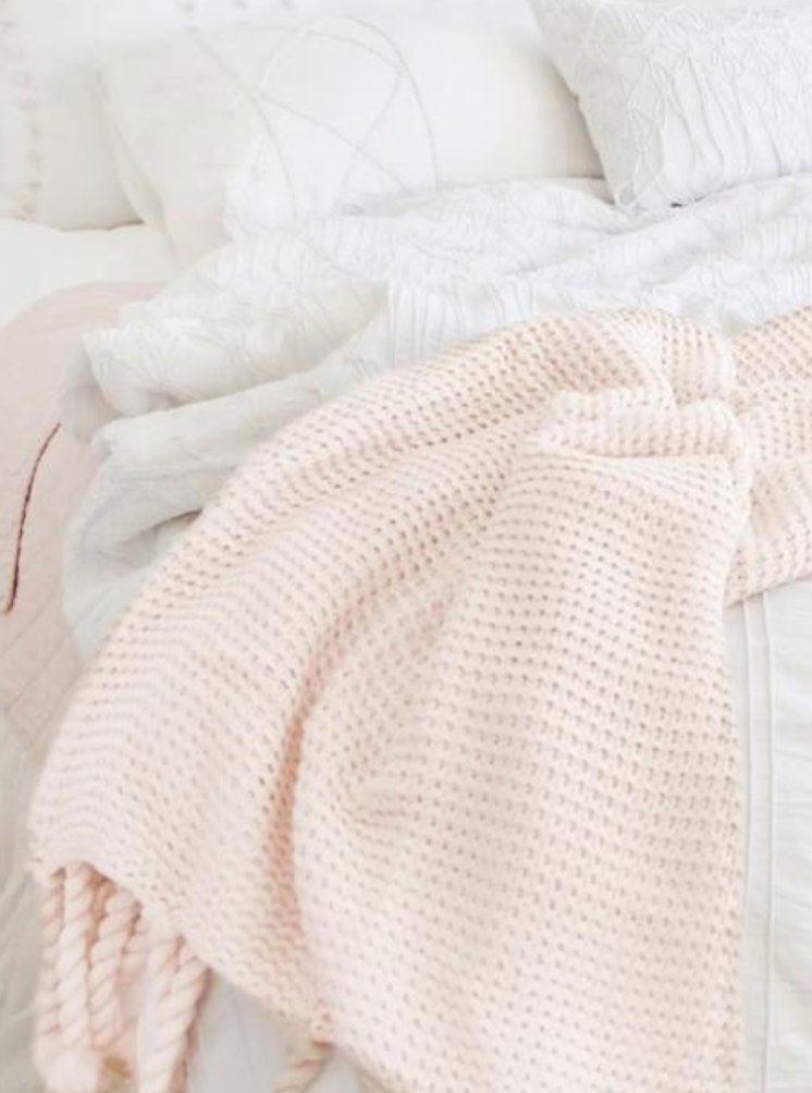 blush colored knit throw on bed with white bedding