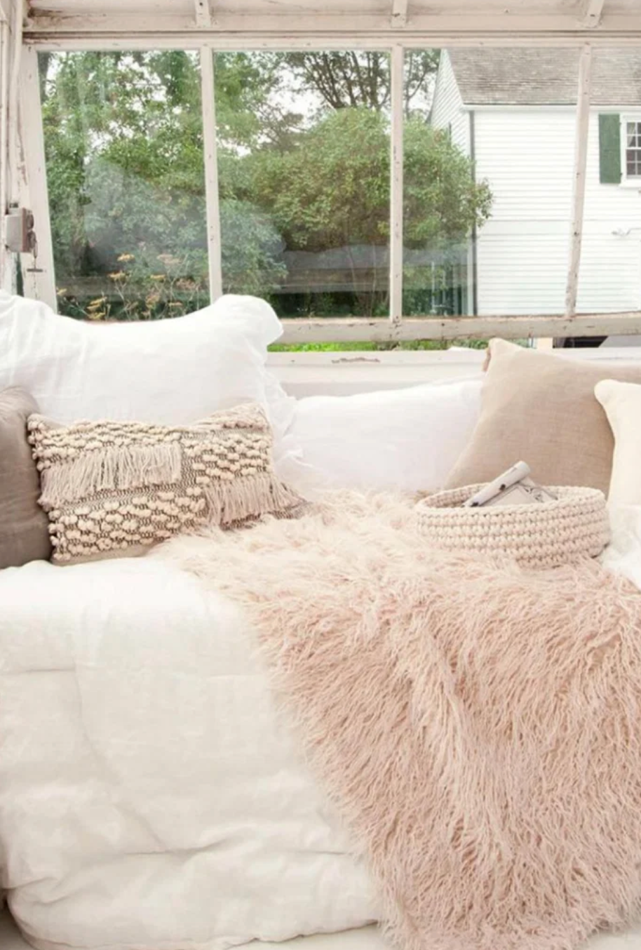a bench in front of a window with shabby chic pillows and blankets on it
