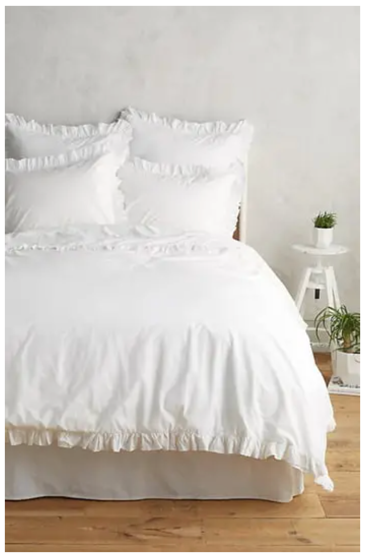 white ruffle bed sheets on a bed