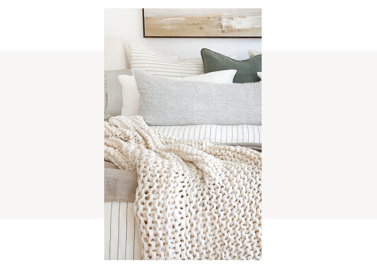 Chunky knit throw blanket on cream striped bed with green pillows