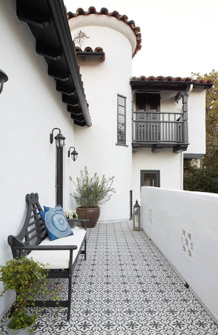 A spainish style home's tiled patio and white turret.