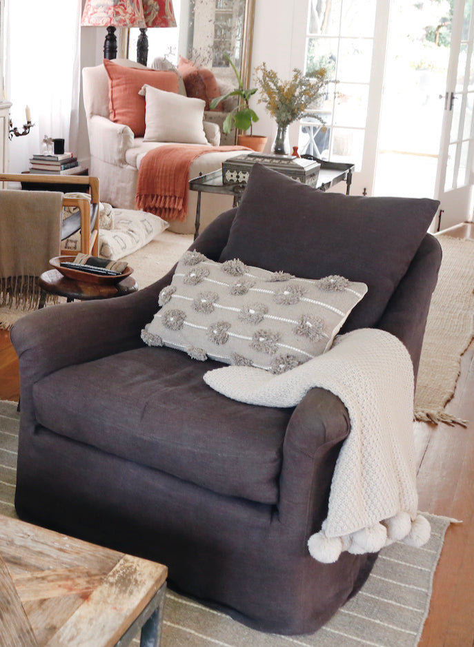 two comfy chairs in a living room with pillows and blankets