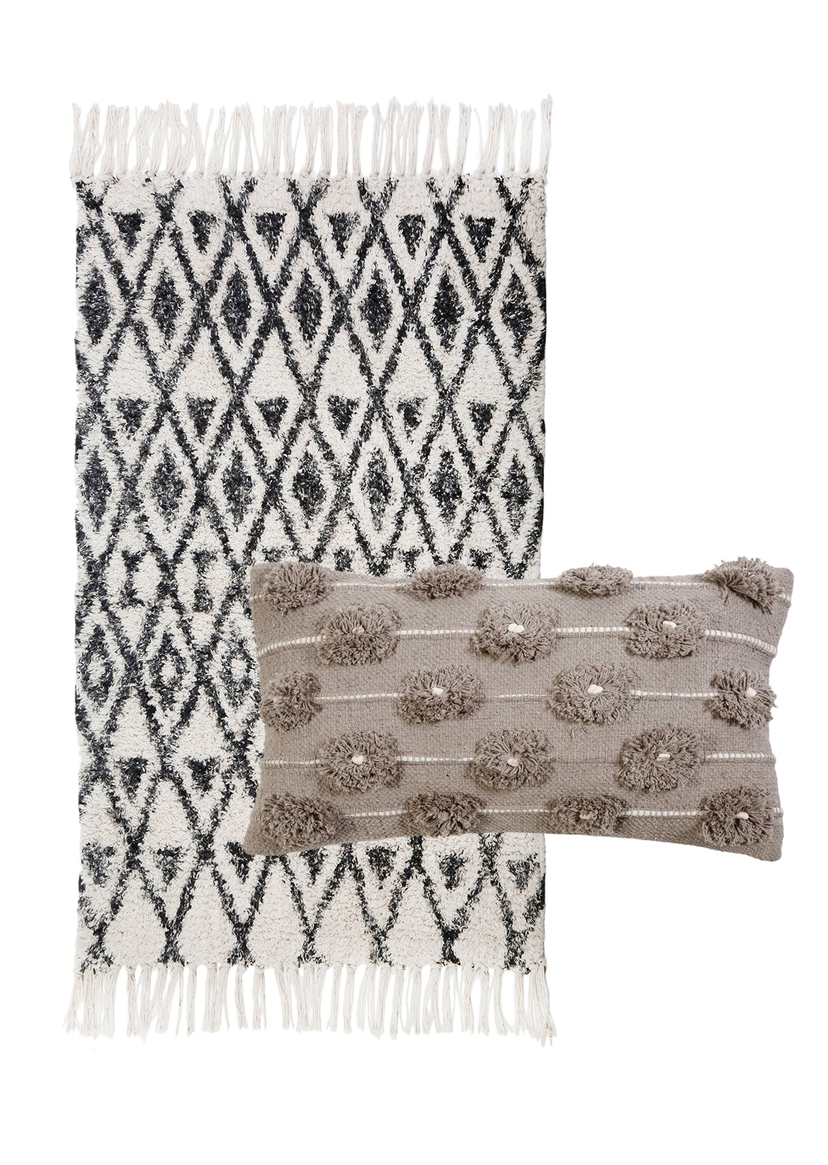 A black and ivory rug with tassels and diamond patterns, with a small pillow in the front. Brown with tassels
